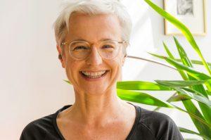 Porträt der Yogalehrerin lachend und mit weißen Haaren